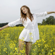 Brunette woman in a yellow flowers field — Stock Photo #12311411