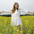Brunette woman in a yellow flowers field — Stock Photo #12311417
