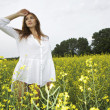 Brunette woman in a yellow flowers field — Stock Photo #12311422