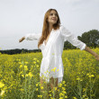 Brunette woman in a yellow flowers field - Stock Photo
