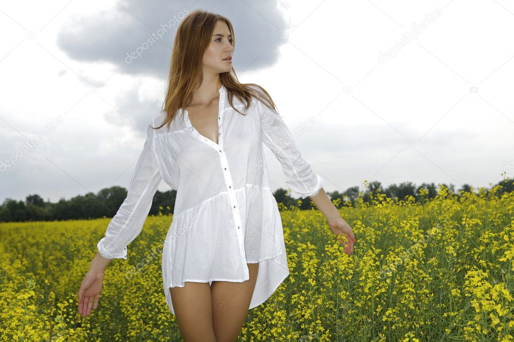 Beautiful and sensuality brunette woman in a yellow flowers field  Stock Photo #12311353