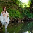 Panorama of a sad bride sitting on a rock — Stock Photo