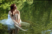 A beautiful bride sitting in water — Stock Photo