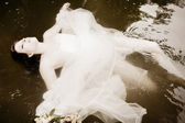 Bride floating in the water — Stock Photo