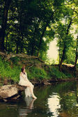 Bride sitting on riverbank — Stock Photo