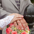 Wedding bouquet and hands with wedding rings — Stock Photo