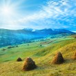 Stock Photo: Morning in mountain with sunshine and haystack