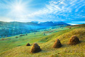 Morning in mountain with sunshine and haystack — Stock Photo