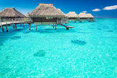 Water villas in the ocean with steps into lagoon — Stok fotoğraf
