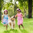 Stock Photo: Two young girls running with golden retriever