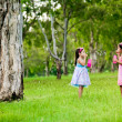 Two sisters blowing bubbles in a park — Stock Photo