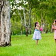 Two sisters blowing bubbles in a park — Stock Photo #11512959