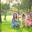 Beautiful little girls and golden retriever — Stock Photo
