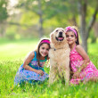 Two young girls hugging golden retriever in the park — Stok fotoğraf