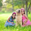 Two young girls hugging golden retriever in the park — Стоковая фотография