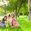 Royalty-Free Stock Photo: Two young girls hugging golden retriever dog