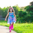 Happy girl riding on roller blades in the park — Stock fotografie