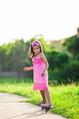 Young girl in pink dress riding on skateboard — Stock Photo