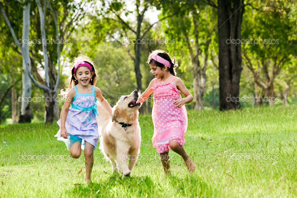 Two young girls running with golden retriever in park  Stock Photo #11512130