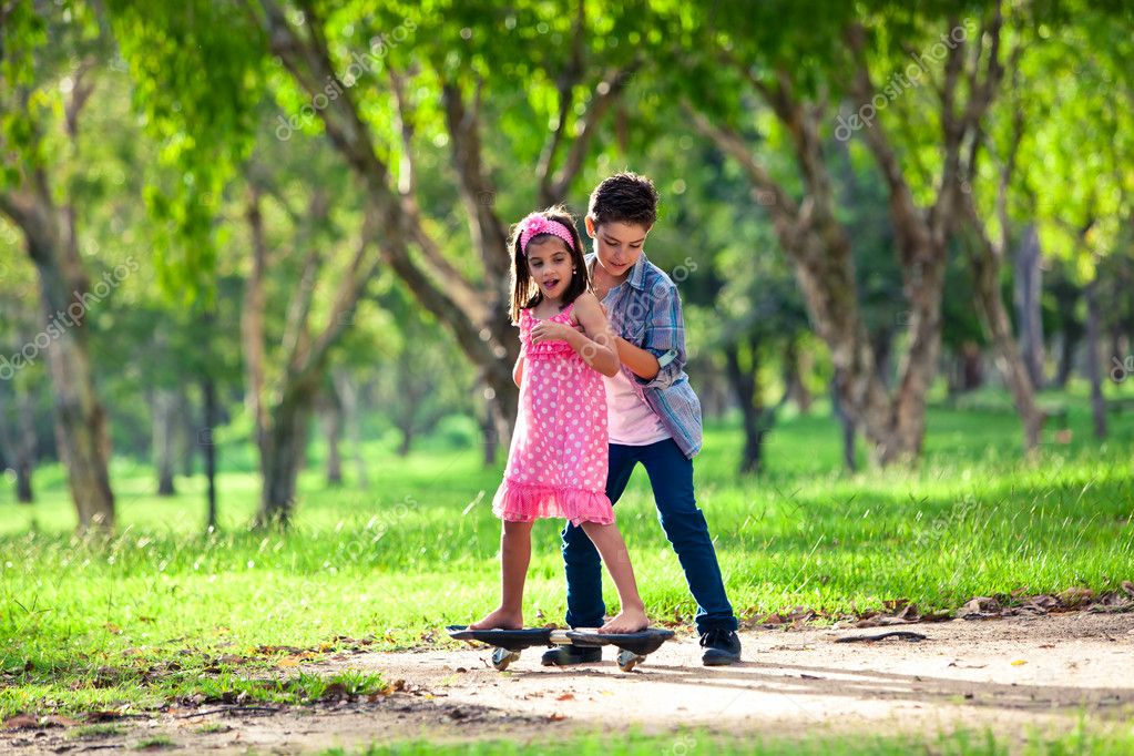 Brother teaching sister how to ride a board in park — Stock Photo #11517207