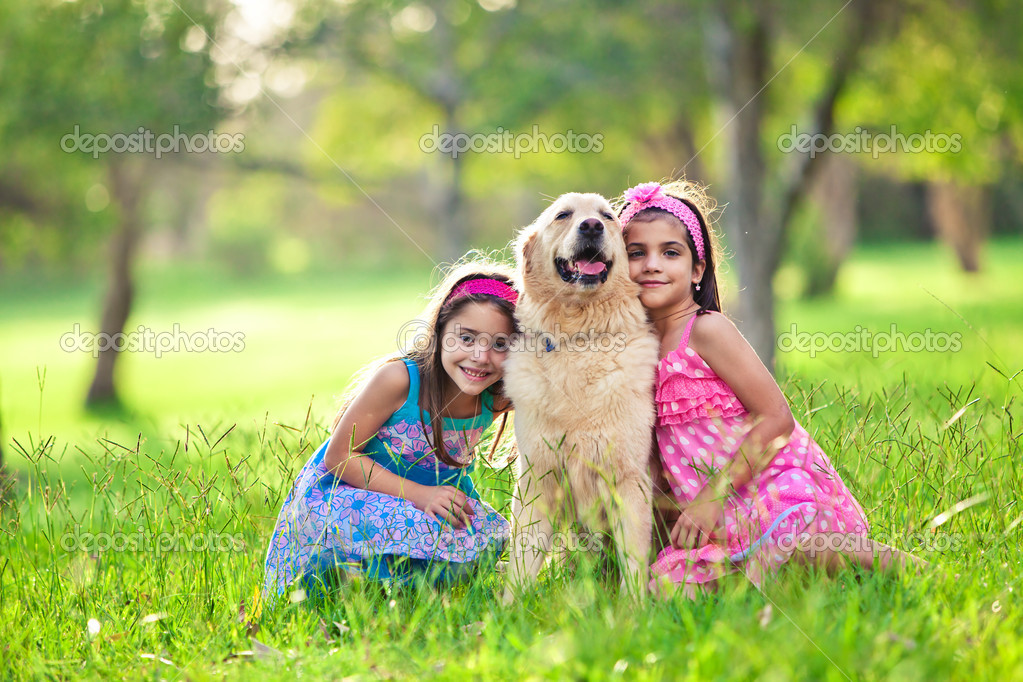 Two young girls hugging golden retriever dog in the park — Stock Photo #11517254