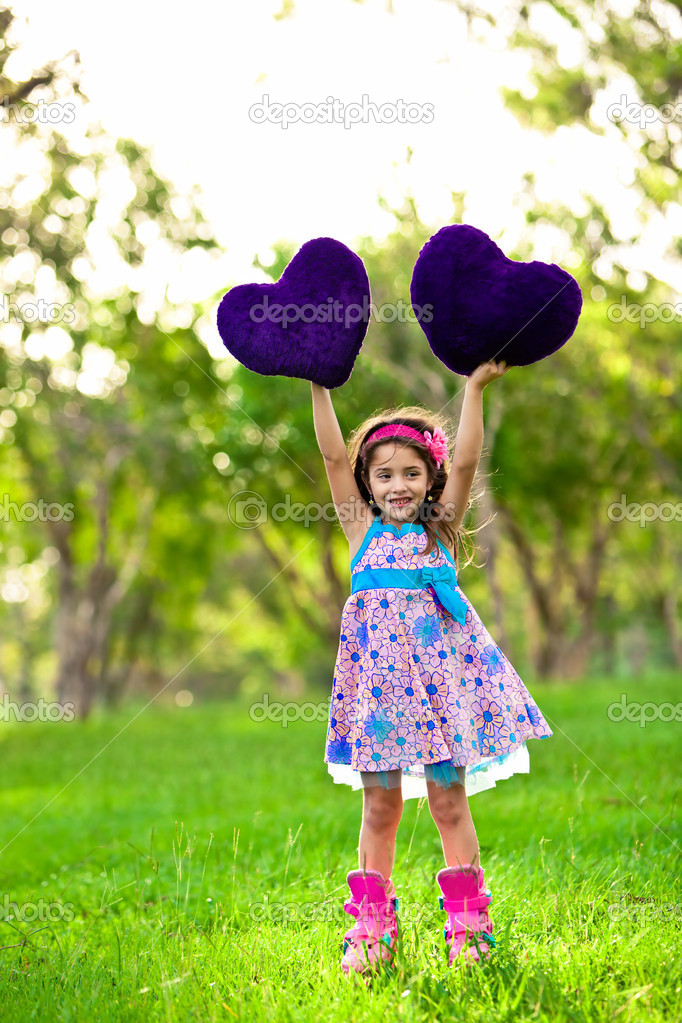 Smilinglittle girl with a heart in the park — Stock Photo #11517500