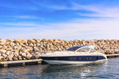 Boat moored in the harbor near a stone dam — Stock Photo