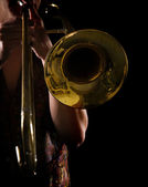 Man playing a trombone, strong contrasting side-light, color version — Stock Photo