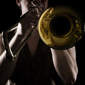 Man playing a trombone; strong contrasting side-light; color version; — Stock Photo
