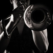 Man playing a trombone; strong contrasting side-light; monochrome version; — Stock Photo