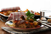 Baked chicken thighs with vegetables on a plate — Stock Photo