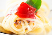 Spaghetti twirled around a fork with ketchup a leaf of basil and — Stock Photo