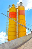 Heaps of granite gravel elimination with yellow silo — Stock Photo