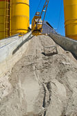 Heap of sand elimination with yellow silo — Stock Photo