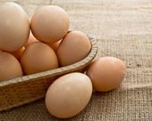 Eggs in a Woven Straw Basket on a burlap Sacking background — Stock Photo