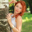 Outdoor portrait of cute red haired young woman — Stock Photo