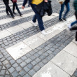 City street with a motion blurred crowd crossing a road — Stock Photo