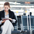 Young female passenger at the airport, using her tablet computer — Stock Photo