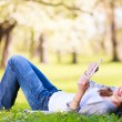 Young woman using her tablet computer while relaxing outdoors — Stock Photo