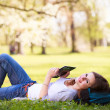 Young woman using her tablet computer while relaxing outdoors — Stock Photo #10957770