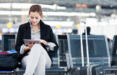 Young female passenger at the airport, using her tablet computer — Stockfoto
