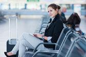 Jonge vrouwelijke passagier op de luchthaven, met behulp van haar tablet-pc — Stockfoto