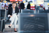 年轻的女乘客在机场使用她的平板电脑 — 图库照片