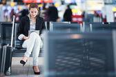 彼女のタブレット コンピューターを使用して、空港での若い女性の乗客 — ストック写真