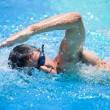 Young man swimming the front crawl in a pool — Stock fotografie