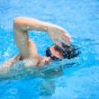 Young man swimming the front crawl in a pool — Stok fotoğraf #11302794