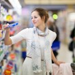 Beautiful young woman shopping for diary products at a grocery s — Stock Photo #11302970
