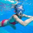 Underwater swimming: young woman swimming underwater in a pool - Stock Photo