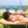 Young man sunbathing and relaxing on a deckchair — Stock Photo #11303090