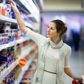 Beautiful young woman shopping for diary products at a grocery s — Photo